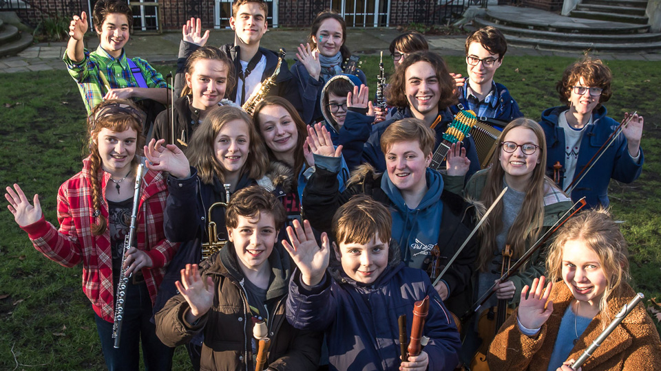 Large group of young musicians waving to camera