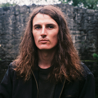 long-haired man standing against a wall