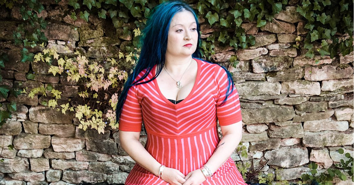 Eliza Carthy - wearing red dress with drystone wall behind