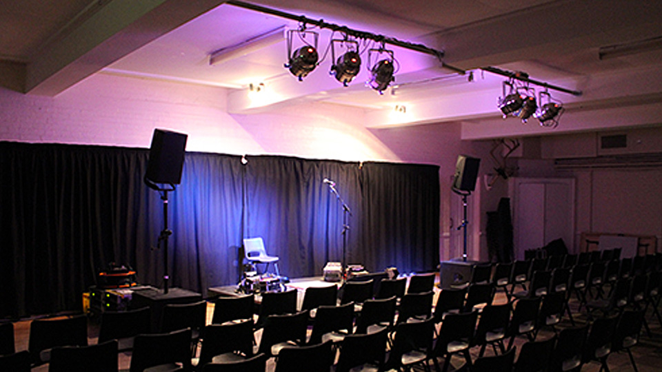 set-up for a gig in Trefusis - dark lighting with rows of chairs facing performance space